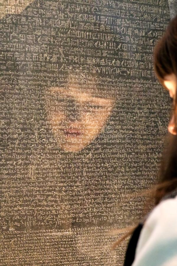 Flickor vänder mot reflekterat som henne försöker att läsa Rosetta Stone med handstil i olika forntida språk - selektiv fokus - i fotografering för bildbyråer