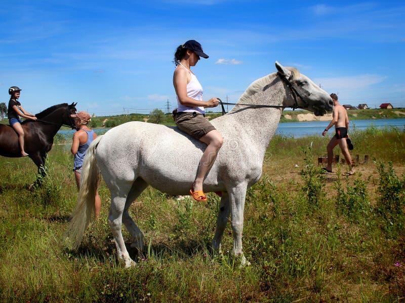 Flickorna på hästrygg Efter ett bad i sjön royaltyfri bild