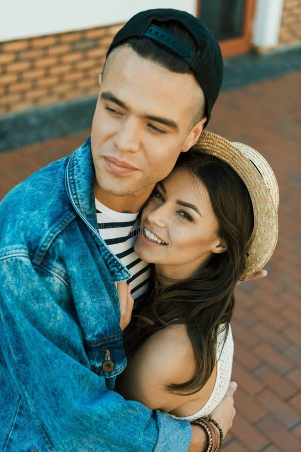 Flickvän i sugrörplatt halmhatt och hennes le pojkvän som kramar på gatan royaltyfri foto