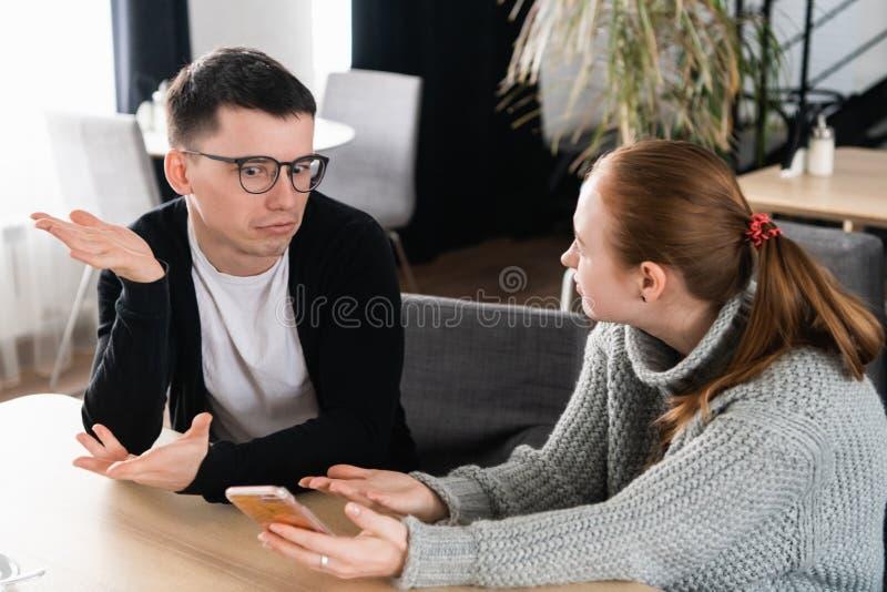 Flickvän som frågar för förklaring av hennes pojkvän som sitter på en soffa i kafét arkivfoto