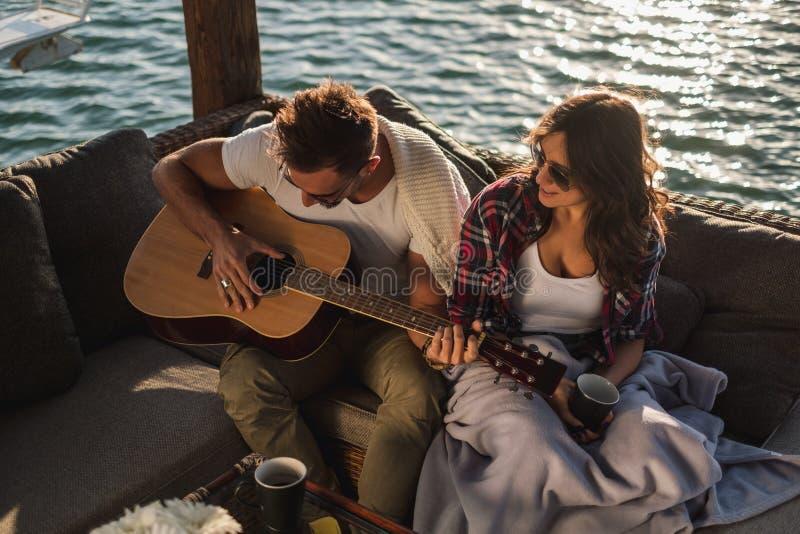 Flickvän som håller ögonen på hennes pojkvän spela gitarren vid floden royaltyfria foton