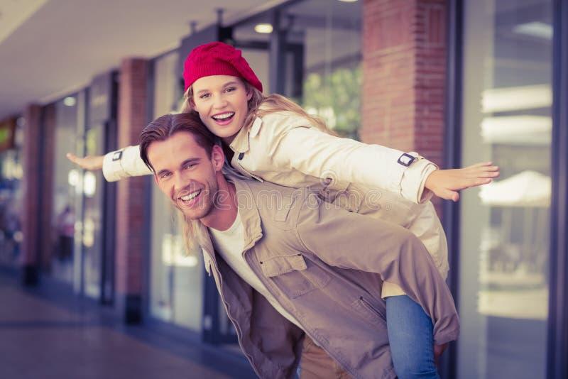 Flickvän som piggybacking på hennes pojkvän arkivfoto