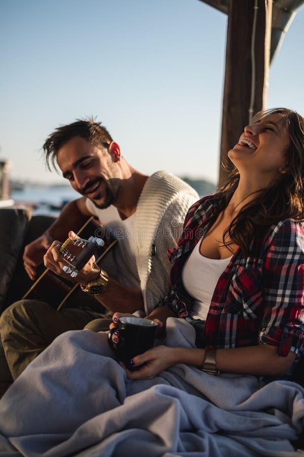 Flickvän som skrattar medan hennes pojkvän som spelar gitarren vid floden royaltyfri foto
