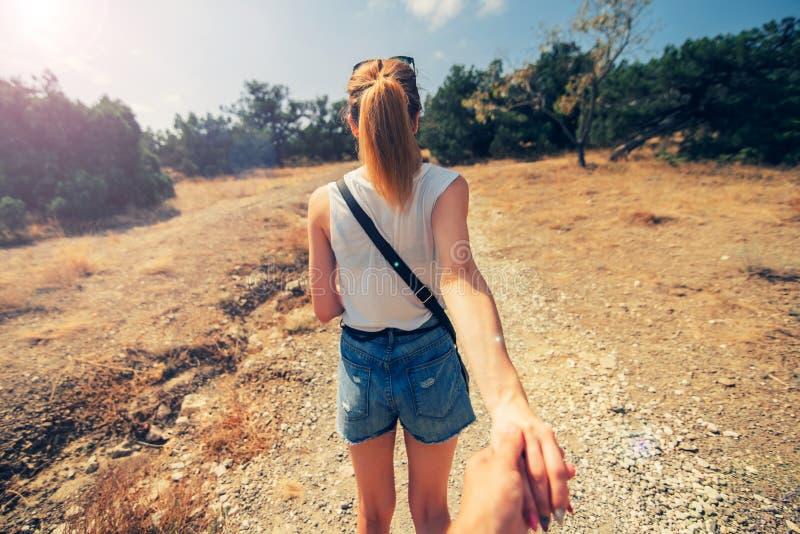 Flickvännen är handen av hennes pojkvän i en fotvandra tur royaltyfria foton