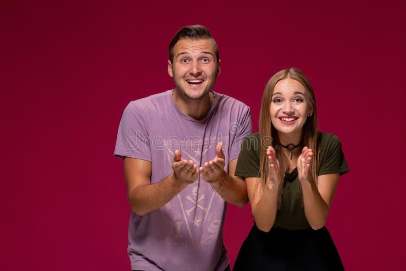 Flickvännen avgjorde med hennes gulliga pojkvän att köpa valpen Inomhus studioskott på burgundy bakgrund royaltyfri bild