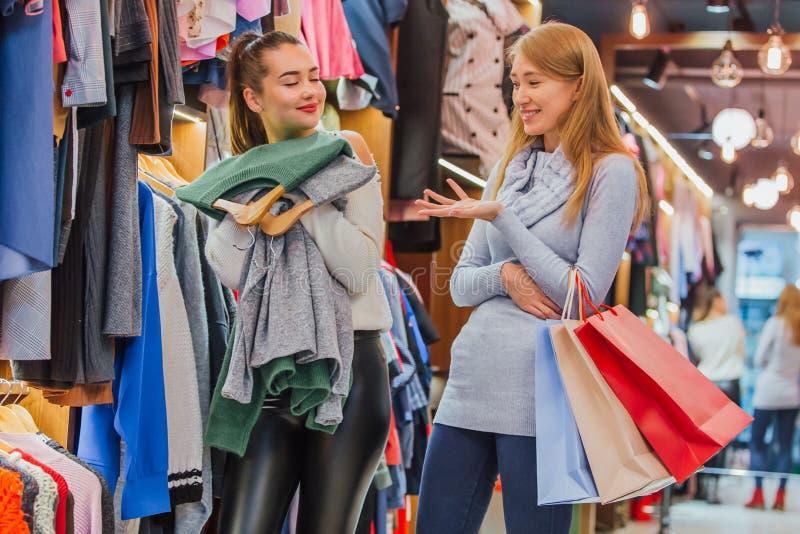 Flickvänner i lagret En rymmer shoppingpåsar arkivbilder