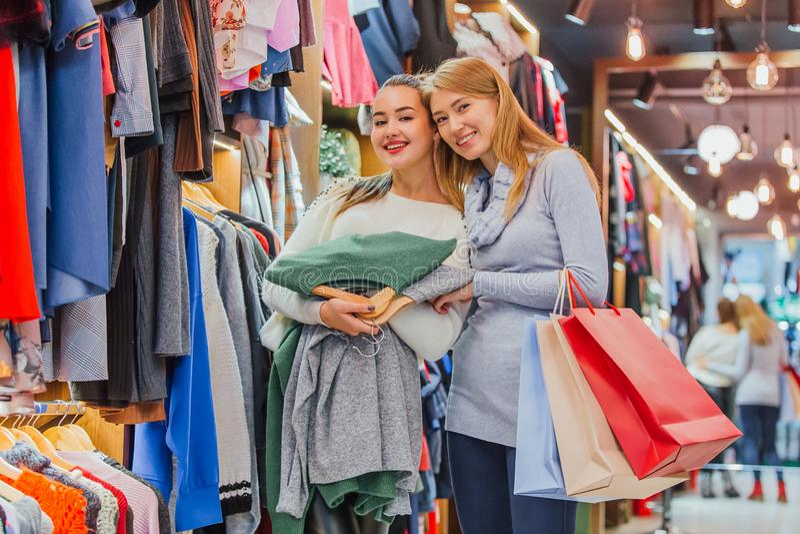 Flickvänner i lagret En rymmer shoppingpåsar royaltyfri foto