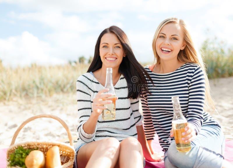 Flickvänner med flaskor av öl på stranden fotografering för bildbyråer