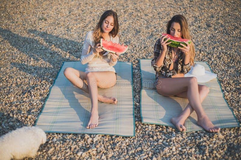Flickvänner som äter vattenmelon på stranden royaltyfri fotografi