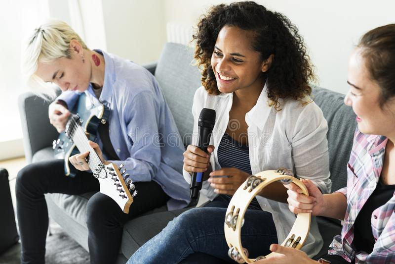 Flickvänner som har gyckel med att spela musik tillsammans royaltyfria bilder
