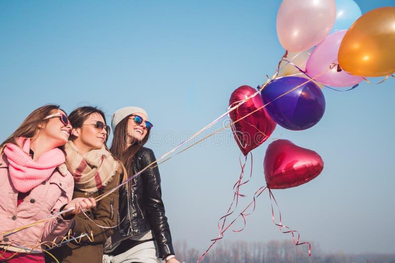Flickvänner som har gyckel med ballonger royaltyfria bilder