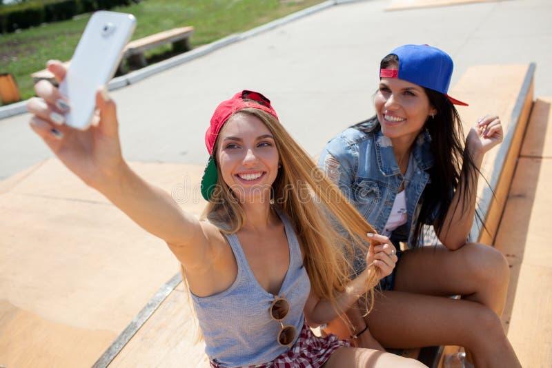 Flickvänner som tar ett selfiefoto på skridskon, parkerar arkivfoto