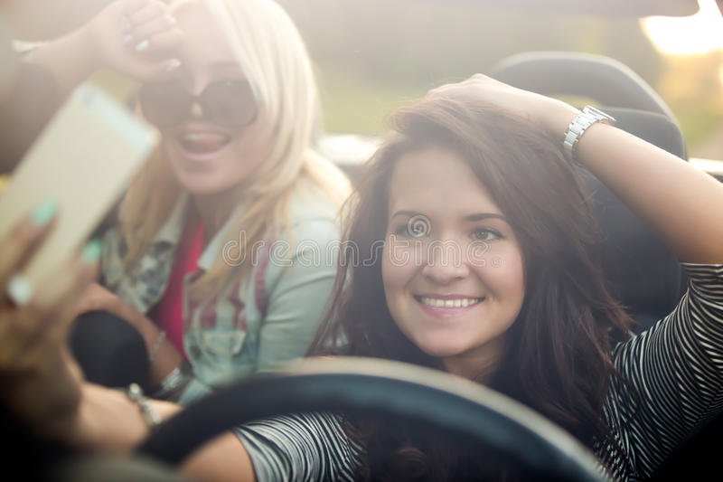 Flickvänner som tar selfie i bil fotografering för bildbyråer