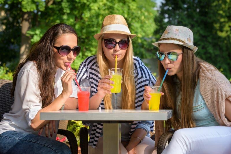 Flickvänner som tycker om coctailar i ett utomhus- kafé, kamratskapbegrepp royaltyfria foton