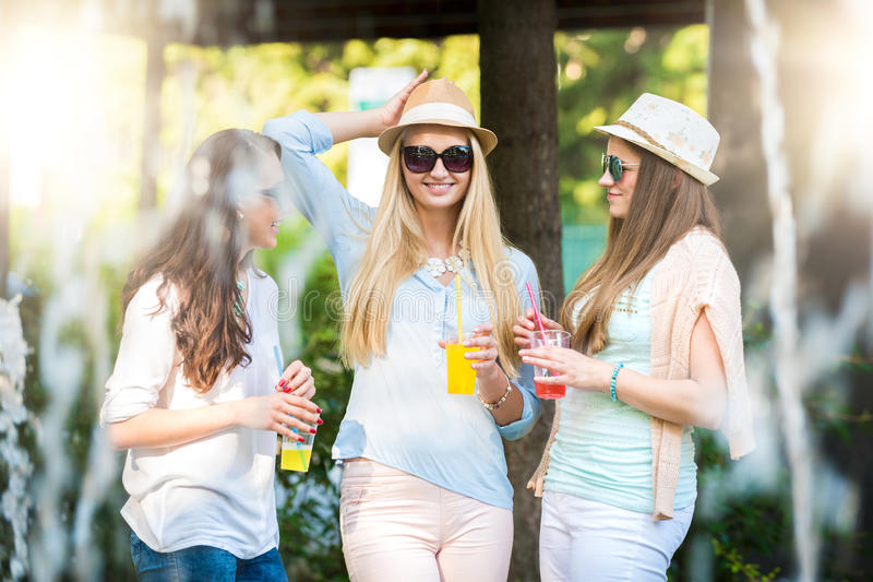 Flickvänner som tycker om coctailar vid en vattenspringbrunn royaltyfria bilder