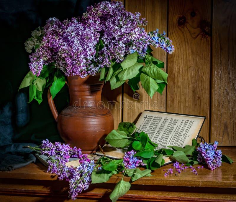 Flieder in einem keramischen Vase, in einem Buch und in einer Stunde auf dem Tisch lizenzfreies stockfoto