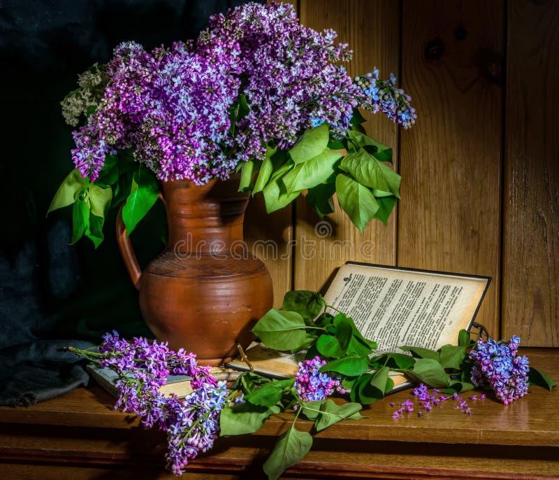 Flieder in einem keramischen Vase, in einem Buch und in einer Stunde auf dem Tisch lizenzfreie stockfotos