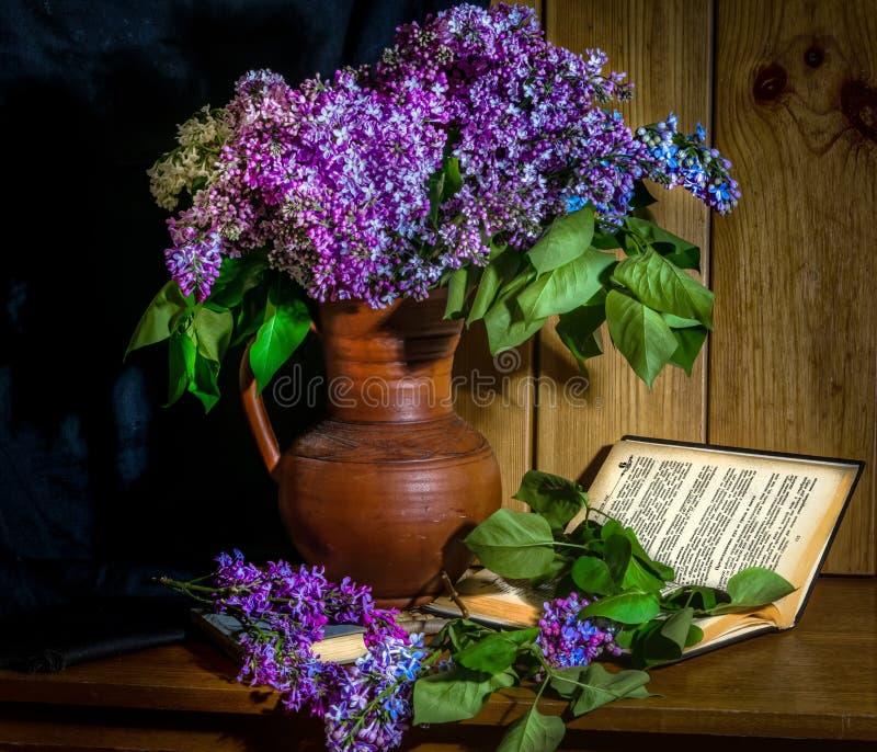 Flieder in einem keramischen Vase, in einem Buch und in einer Stunde auf dem Tisch stockfotos