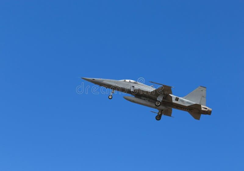 Fliegen des Kampfflugzeugs F5 auf Hintergrund des blauen Himmels stockfotografie