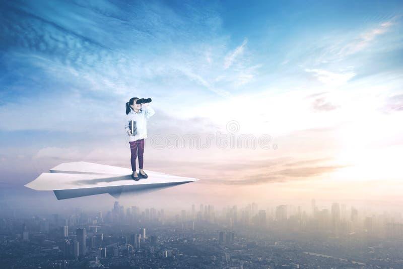 Fliegen des kleinen Mädchens mit Papierflugzeug stockfotografie