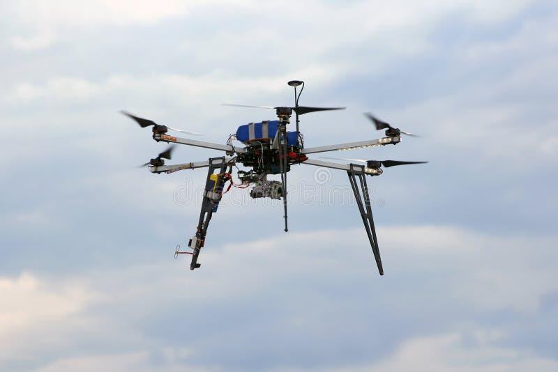 Fliegenbrummen im Himmel mit angebrachter Digitalkamera stockbild