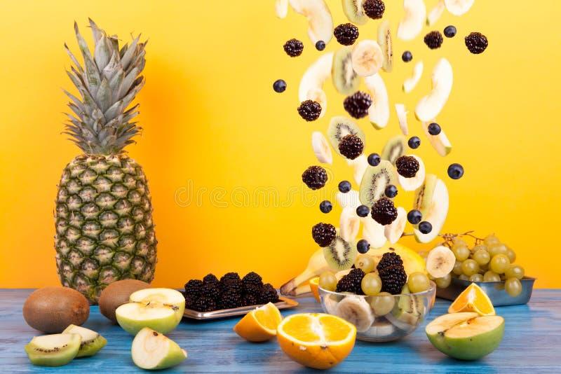 Fliegende geschnittene Früchte in der Glasschüssel mit Obstsalat lizenzfreies stockfoto