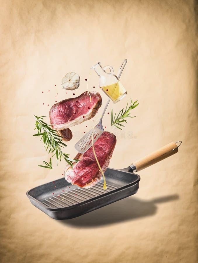 Fliegende rohe Rindfleischfleischsteaks, mit Kräutern, Öl und Gewürzen mit Grillwanne und Küchengeräten, am natürlichen beige Hin stockbilder