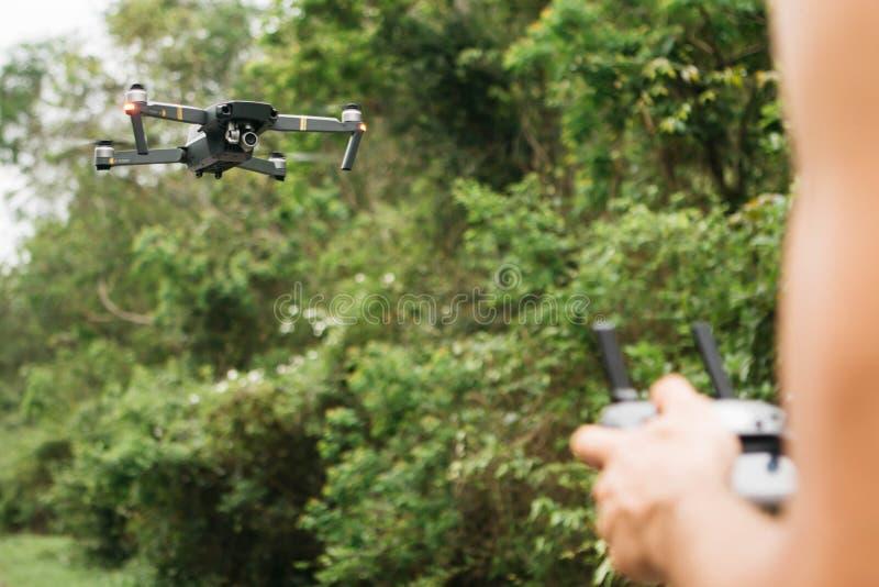 Fliegendes Brummen auf dem Fokus und unscharfen H?nden, die einen Steuerfernmann auf einem Gebiet halten lizenzfreie stockfotos