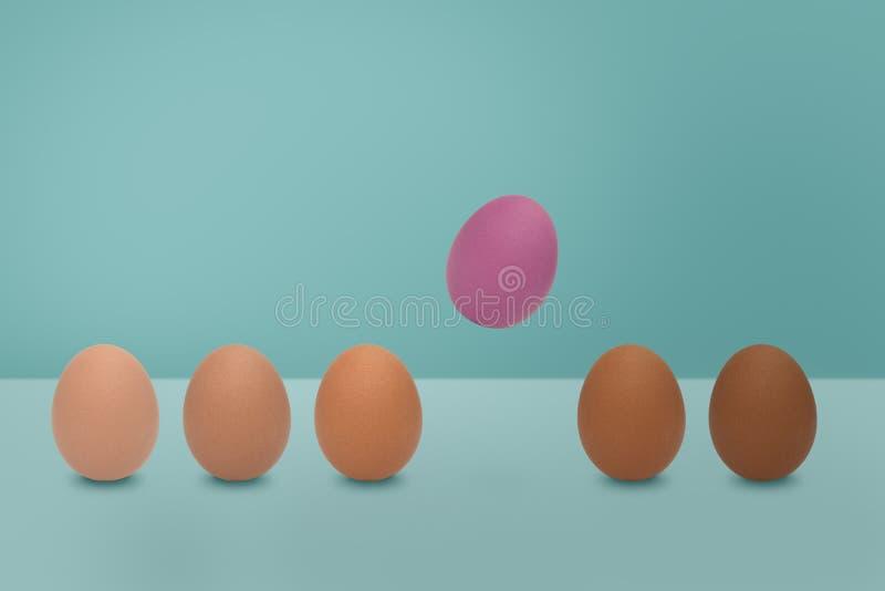 Fliegendes rosa Ei und unterschiedliche Schattenfarbe von Eiern auf blauem Hintergrund Minimale Ostern-Idee lizenzfreie stockbilder
