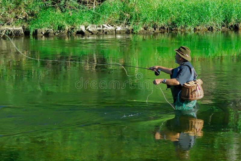 Fliegenfischer im Fluss nach Forelle lizenzfreies stockbild