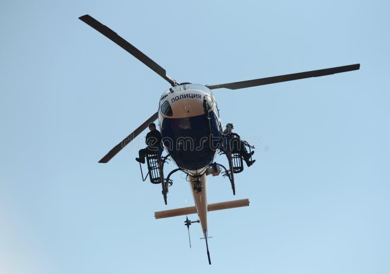 FLIEGENKLATSCHE-Kämpfer auf einem Polizeihubschrauber AS-355 lizenzfreie stockbilder
