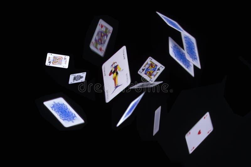 Fliegenpokerkarten auf schwarzem Hintergrund lizenzfreie stockfotografie
