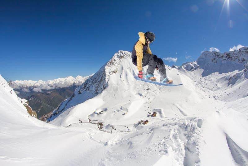 Fliegensnowboarder auf Bergen, extremer Sport lizenzfreie stockbilder