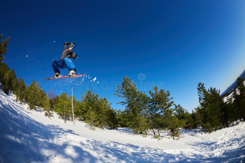 Fliegensnowboarder in den Bergen stockfotografie