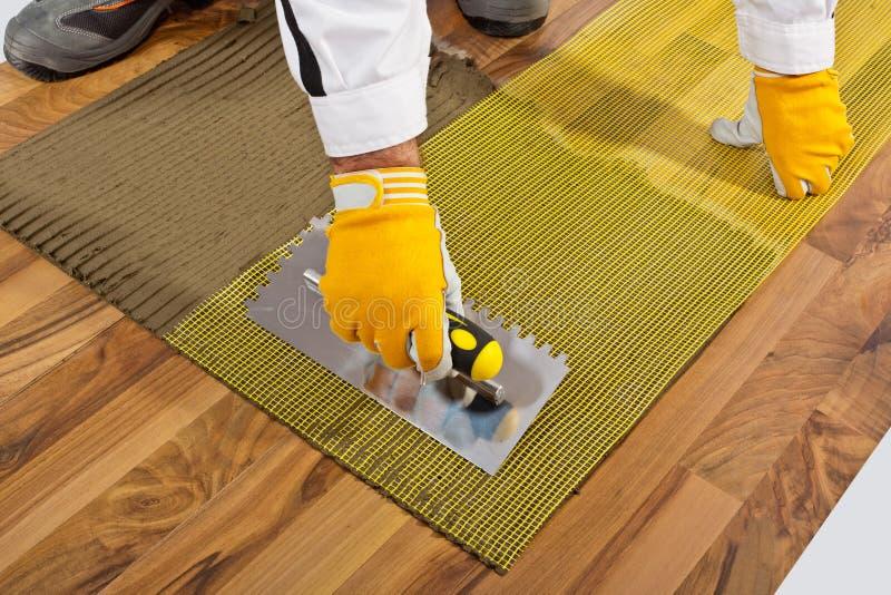 Fliesekleber mit Trowel auf hölzernem Fußboden lizenzfreies stockbild