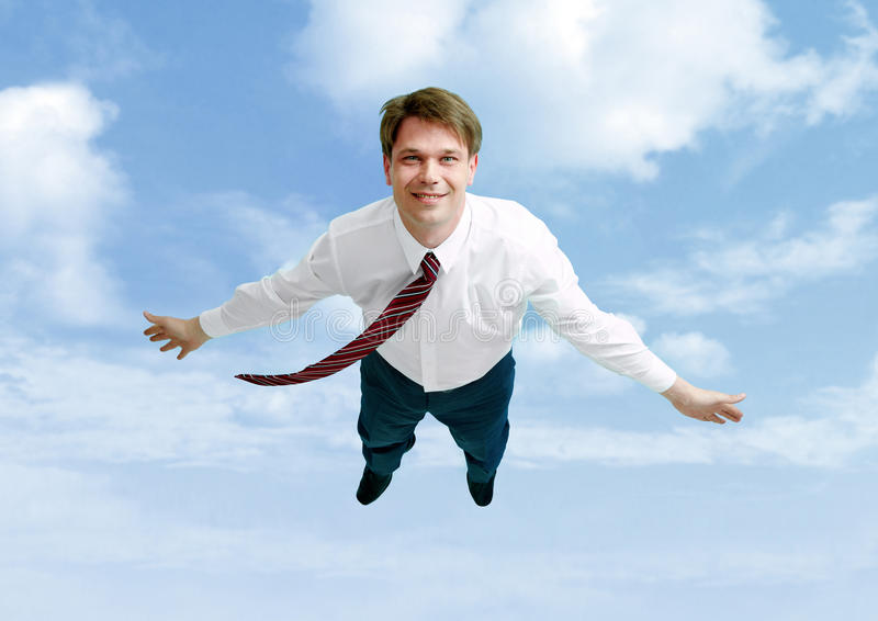 Flight. Conceptual image of happy businessman flying in the clouds royalty free stock image