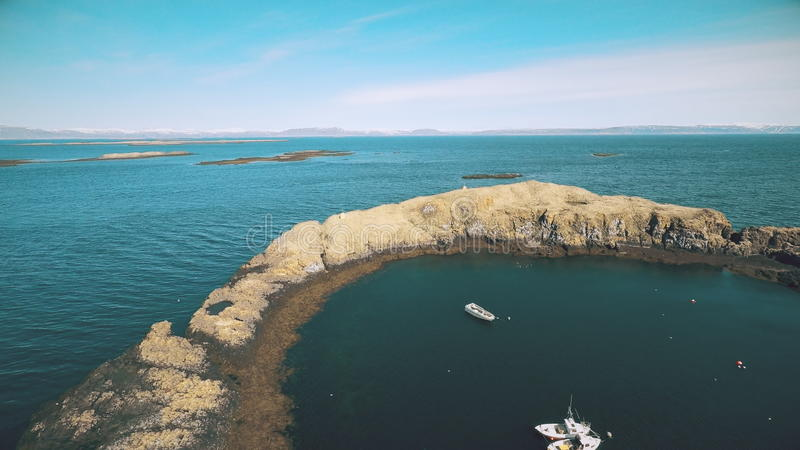 Flight along the coast of the island Vigur. The island is a home for thousands of birds e.g. eider ducks, arctic terns, puffins, black guillemot and more. The stock footage