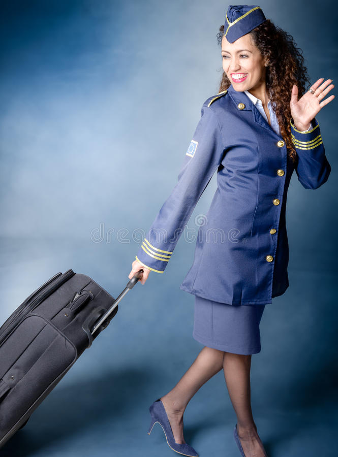 Flight attendant. dragging luggage and waving goodbye royalty free stock photos