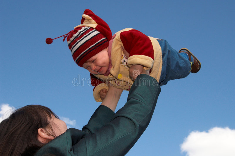 Flight baby. The mother and child on a background of the dark blue sky royalty free stock photography