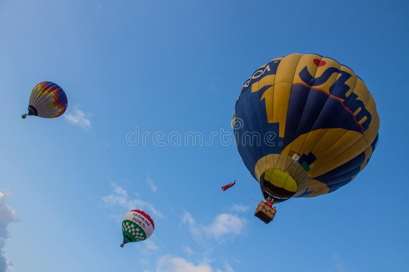 Flying balloon with passengers in a basket against the blue sky at the festival of Aeronautics summer evening in Pereslavl-Zalessk. Flight balloon with stock image