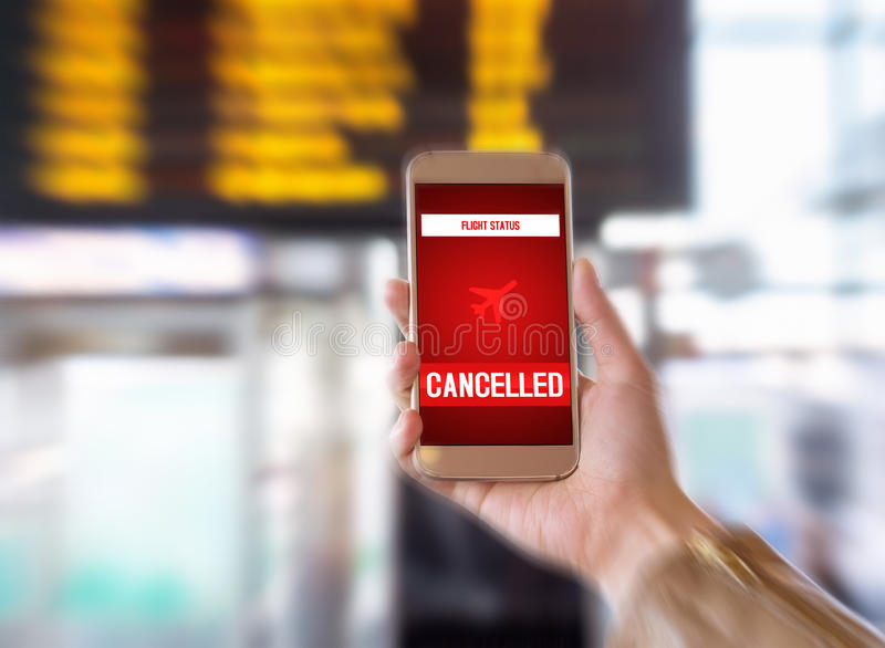 Flight cancelled. Smartphone application announces bad news to tourist. Strike or problem with plane. Woman holding mobile phone in airport terminal. Timetable stock photos