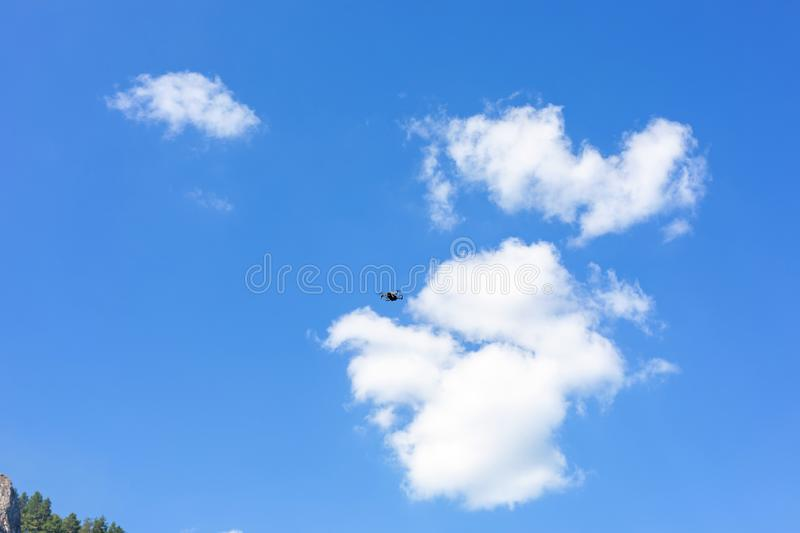 Flight of the drone against the blue sky on a sunny day. quadcopter flying. New aerial photo and video technology. Flight of the drone against the blue sky on a royalty free stock image