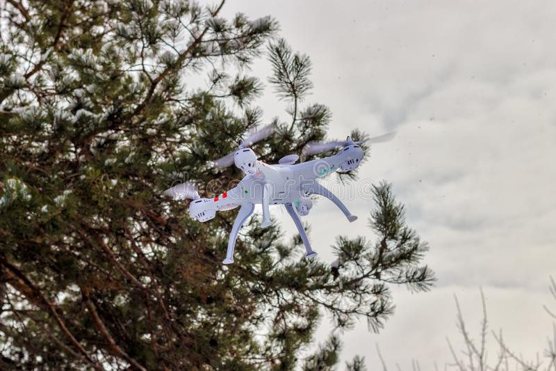 Flight of the drone in the winter forest. The concept of unmanned aerial vehicles. UAV, technology and observations royalty free stock photography