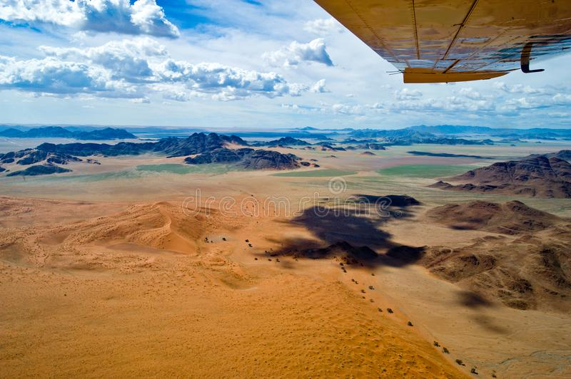Namibia, flight over Sossusvlei. Border of orange dunes and rocks seen from plane, aerial view royalty free stock image