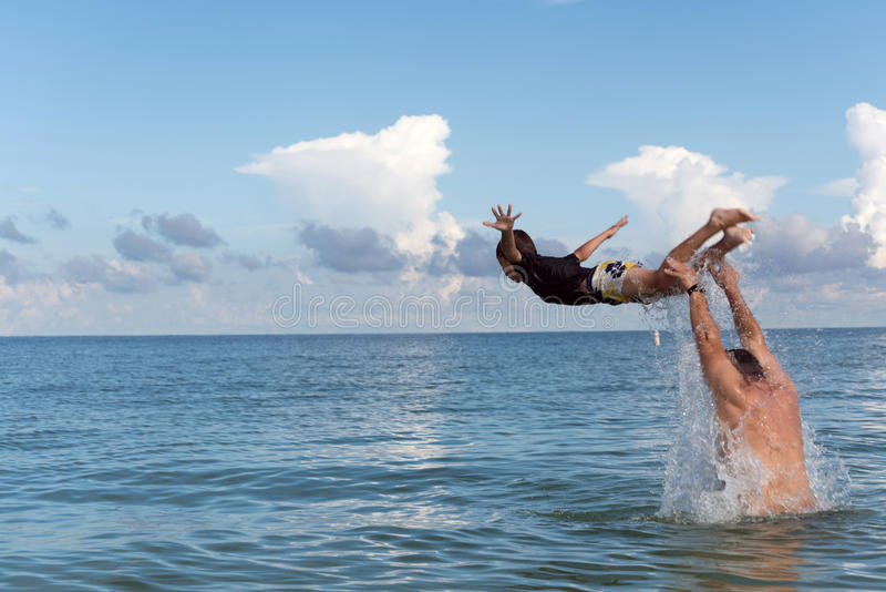 Flight over the water, Clearwater beach, Florida, USA. Dad throws his son out of the water playing with him on the beach, Florida, USA stock image