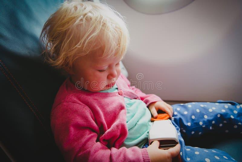 Flight safety - little girl fasten seat belt in plane stock photo
