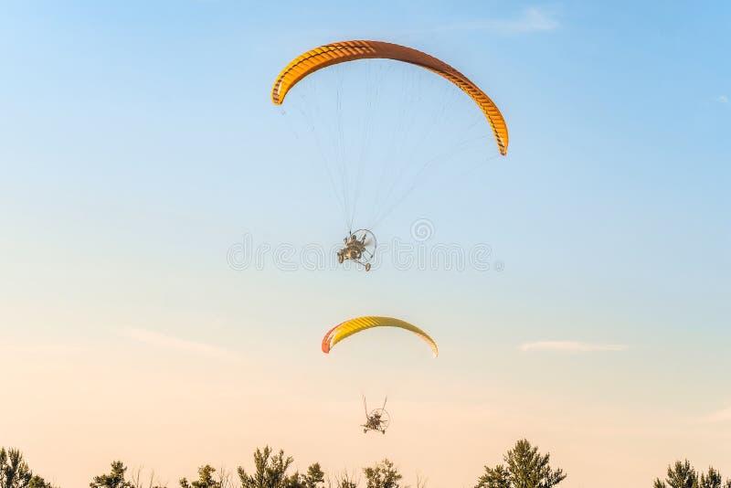 Flight of two motor paragliders trike skyward royalty free stock photos