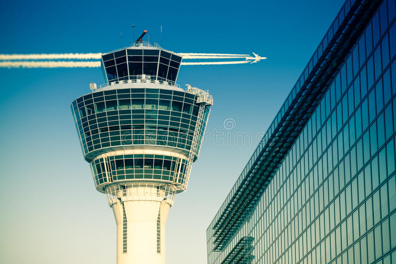 Flights management air control tower passenger terminal and flying plane. Flights management air control tower and passenger terminal in Munich international royalty free stock photography