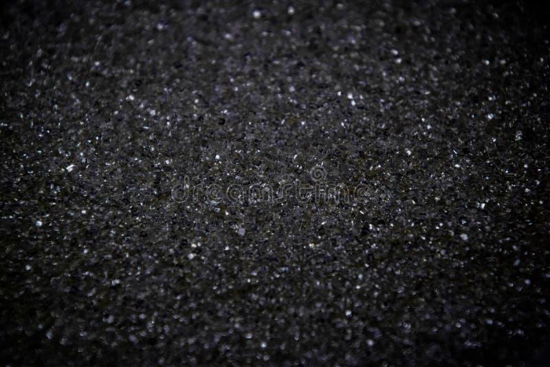 Flingor för vitt socker vänder in i svart våg som färg-kodifieras med en fotoredaktör svart f?rgbakgrund royaltyfria foton