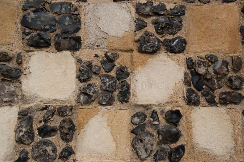 Flint and Sandstone Chequer Board Wall Construction Detail. Detail of unusual wall construction using regular squares of sandstone and flints. This type of royalty free stock photography